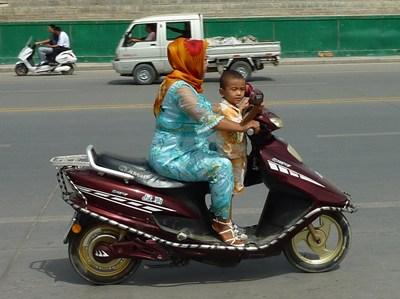 電動バイクの前に乗る子ども